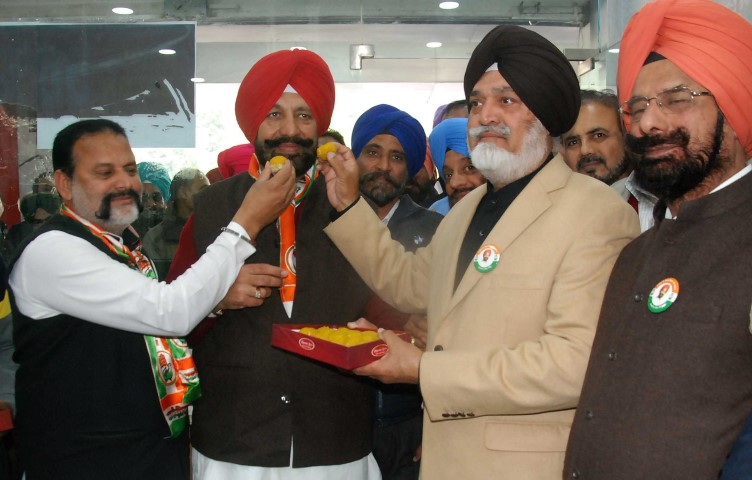 Col Ranjit Singh  Boparai, (retired)  offers ladoo, to  Balbir Singh Sidhu, former MLA and congress candidate from Mohali, at the inaguration of congress   election office at Phase V11 Market in Mohali on Tuesday.